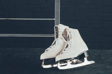 pair of white figure skates on gray floor