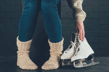 cropped image of woman taking skates from floor