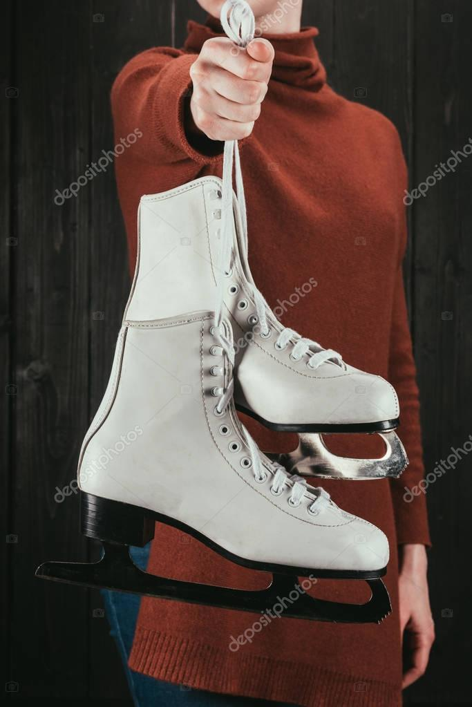 cropped image of woman holding skates with shoelaces