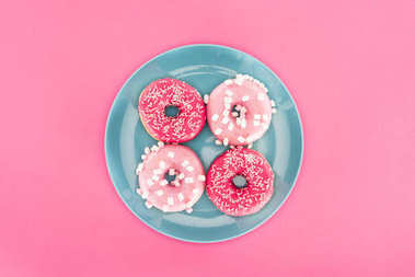 Top view of glazed doughnuts on plate isolated on pink stock vector