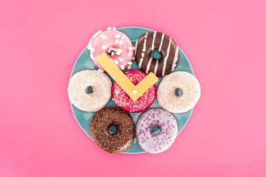 Top view of clock made of doughnuts on plate isolated on pink