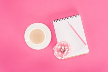 top view of glazed doughnut with cup of coffee and blank notebook on pink surface