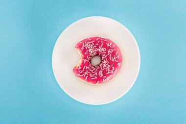 top view of bitten pink glazed doughnut on plate