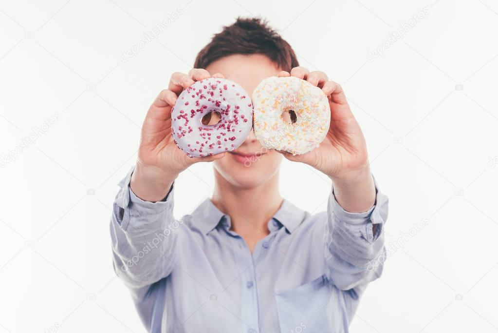 smiling woman covering eyes with tasty doughnuts isolated on white