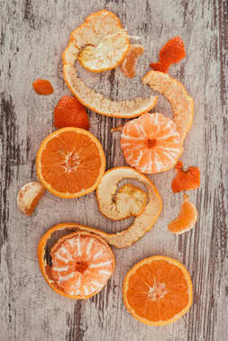 top view of arranged mandarins, orange pieces and citron on shabby wooden surface