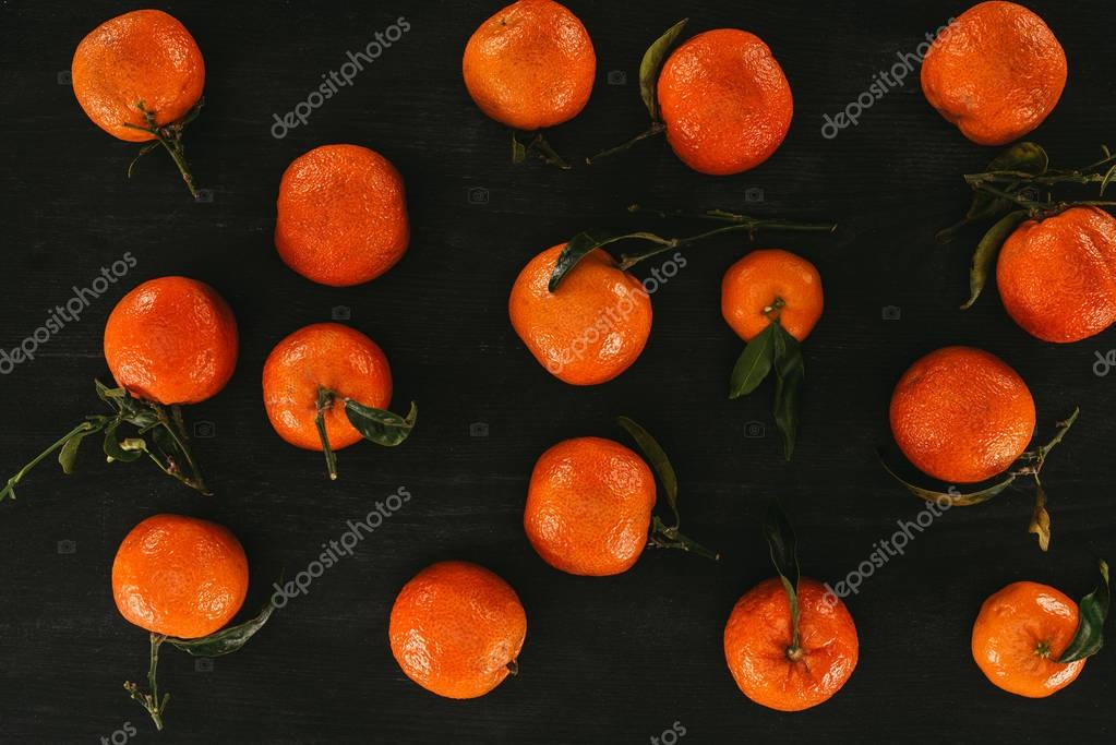 flat lay of arrangement of mandarins with leaves on black wooden surface
