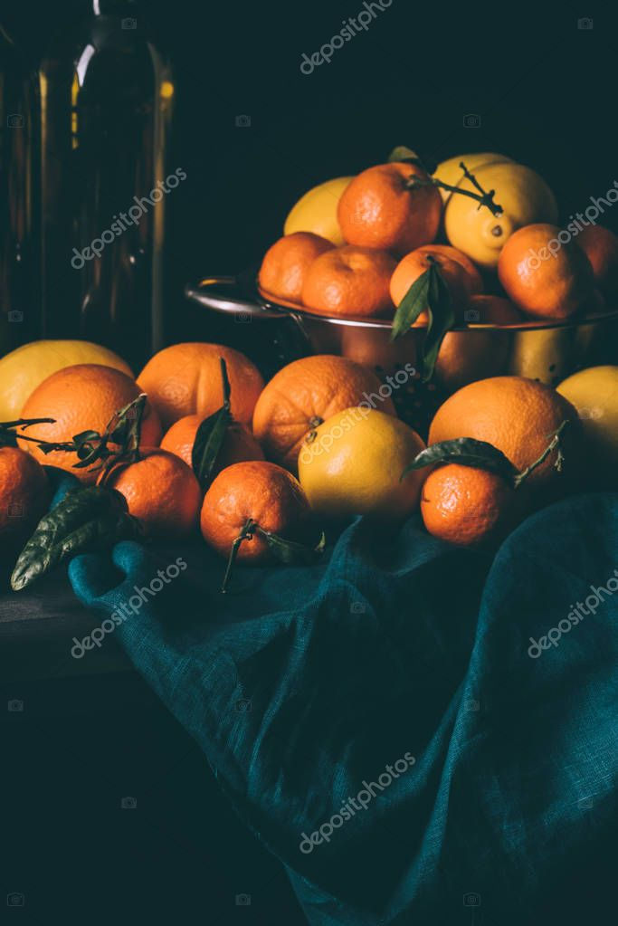 close up view of pile of lemons and tangerines with leaves in strainer on dark surface