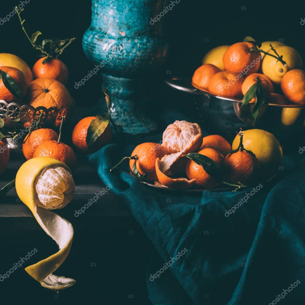 close up view of arrangement of fresh lemons and tangerines in bowl and strainer on table with dark tablecloth