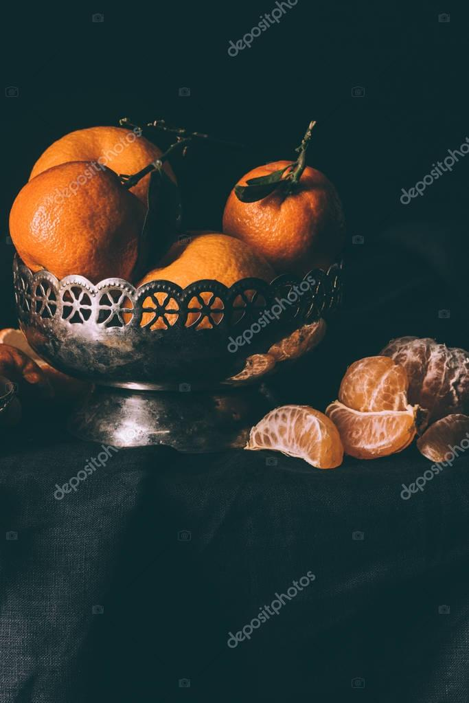 close up view of fresh mandarins in metal bowl on table with dark tablecloth