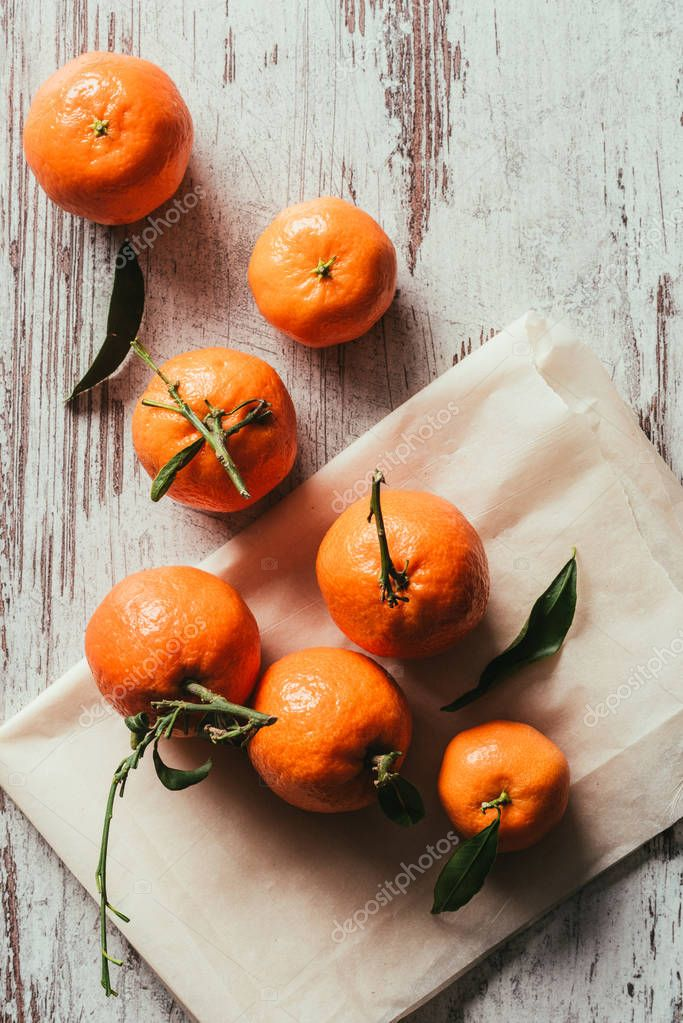 top view of tangerines with leaves on baking paper on rustic tabletop