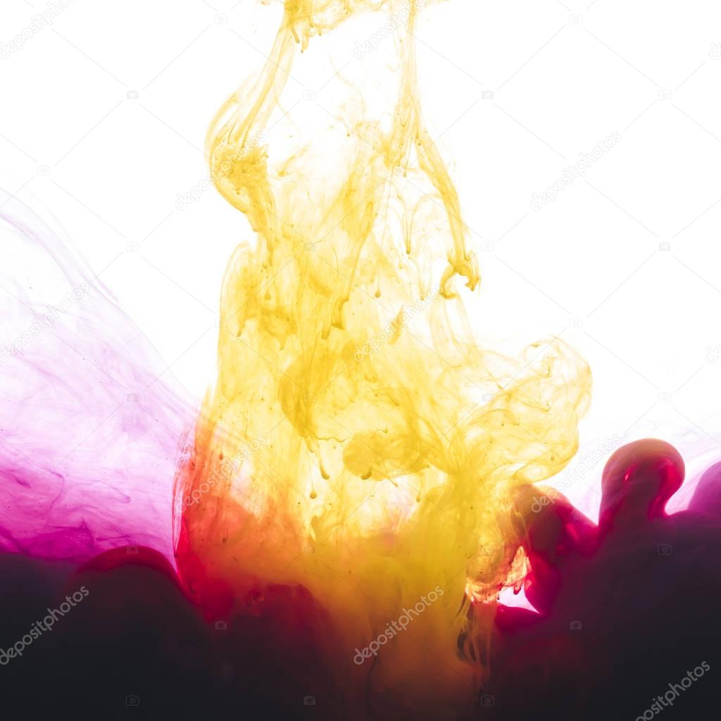 close-up view of pink and yellow paint splashes isolated on white