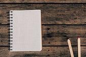 Pohled shora složení barevných tužek s prázdnou notebook na dřevěné pozadí