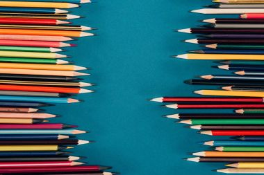 Frame of colorful pencils isolated on blue background
