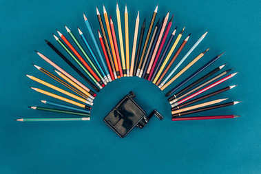 Top view of composition of colorful pencils and sharpener isolated on blue background