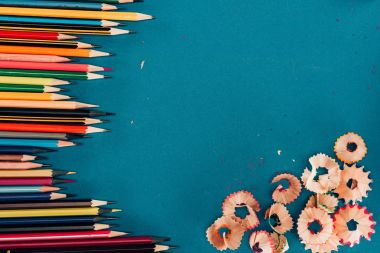 Top view of composition of colorful pencils and cuttings isolated on blue background