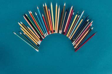 Top view of composition of colorful pencils isolated on blue background