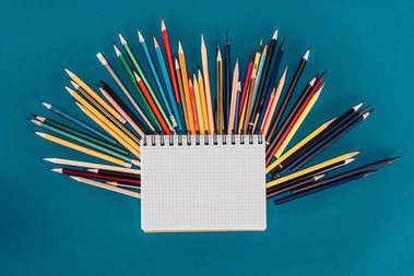 Top view of composition of colorful pencils with blank notebook isolated on blue background
