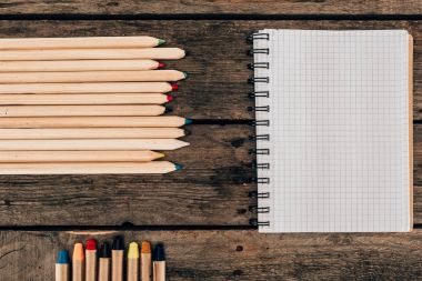Top view of composition of colorful pencils with blank notebook on wooden background