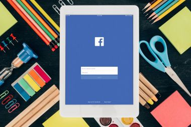Flat lay tablet with Facebook app over background with school supplies isolated on dark