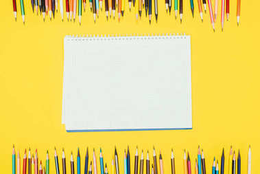 Top view of frame of colorful pencils isolated on yellow background with notebook