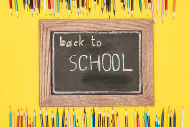 Top view of Back to school inscription on chalk board with pencils