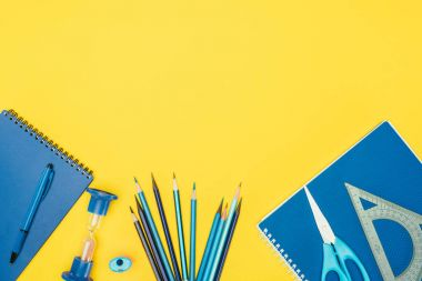Top view of composition of colorful school supplies isolated on yellow background