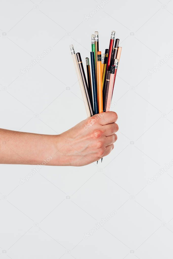 Close-up view of female hand with colorful pencils isolated on white background