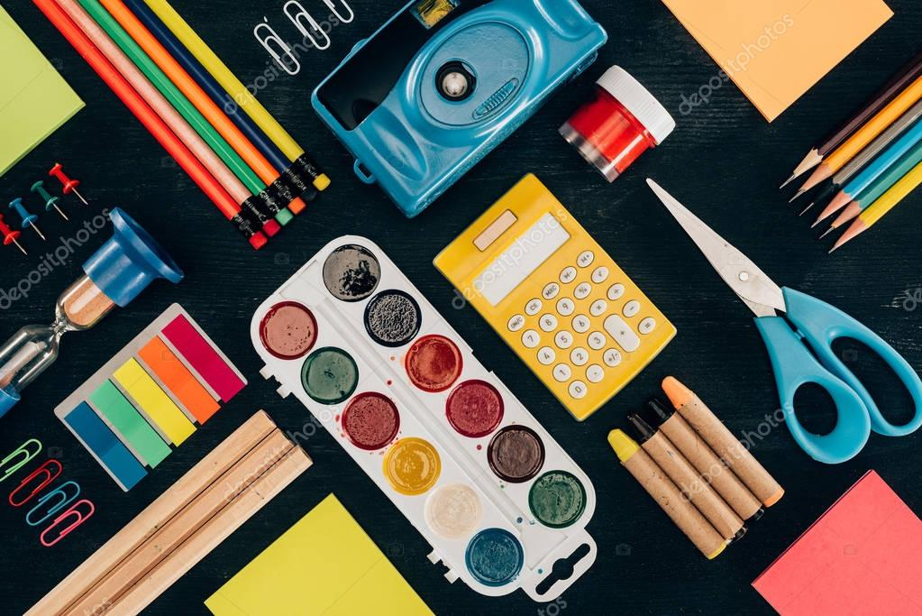 Flat lay composition of colorful school supplies isolated on dark board background