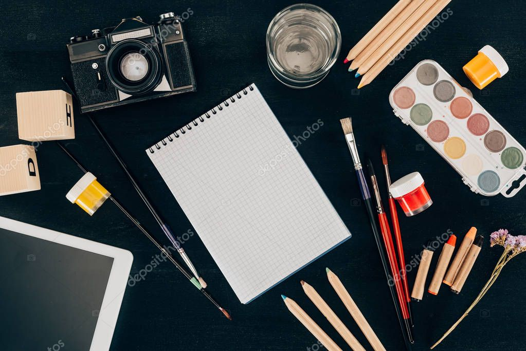 Top view of composition of colorful school supplies with blank notebook isolated on dark board background