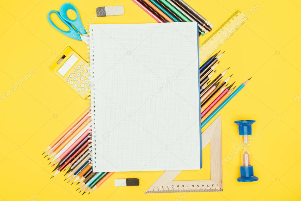 Top view of composition of colorful school supplies with blank notebook isolated on yellow background