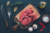 top view of raw steak on parchment paper and cutting board with spices and cutlery around