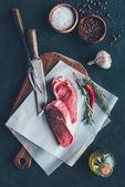 Ansicht von rohen Fleischscheiben auf Pergamentpapier und Schneidebrett mit Besteck
