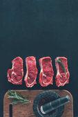 Ansicht von rohen Steaks in Reihe mit Gewürzen auf Holzbrett