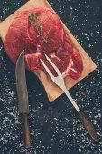 Fotografie Ansicht von rohem Steak mit Gabel und Messer auf Holzbrett