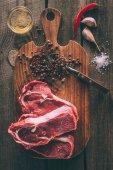 Draufsicht auf einen Haufen Steaks mit Gewürzen auf einem Holzschneidebrett