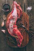pohled shora na syrové vepřové maso s kořením na dřevěném prkénku