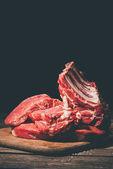 Fotografie verschiedene rohe Fleischsorten auf einem Holzschneidebrett auf schwarz