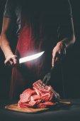 řezník s nožem a vidličkou řezání syrového masa na dřevěném prkénku
