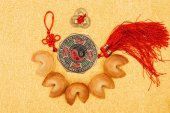 Fotografie top view of chinese talisman surrounded with fortune cookies on golden surface, Chinese New Year concept