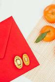 Fotografie Draufsicht der roten Umschlag mit Mandarinen und chinesischen goldenen Barren, Chinese New Year-Konzept