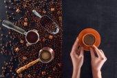 částečný pohled shora osoby držící šálek kávy a pražených kávových zrn s kávové konvice, lopatka a cukru