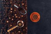 pohled shora na kávu s podšálkem, pražená kávová zrna, hnědý cukr, kávové konvice a lopatka na černém pozadí