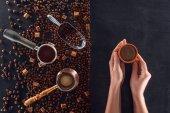 pohled shora osoby držící šálek kávy a pražených kávových zrn s kávové konvice, lopatka a cukru