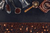 top view of roasted coffee beans with brown sugar and various coffee makers and grinders on black