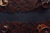 pohled shora pražená kávová zrna, pytloviny, mlýnek na kávu a lopatka na černém pozadí