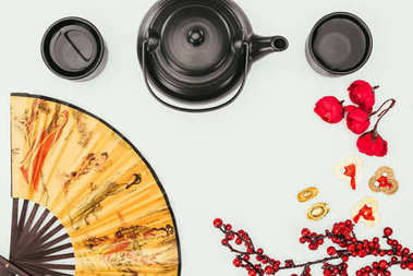 top view of chinese new year composition with tea and handheld fan isolated on white