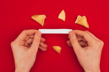 cropped shot of woman opening traditional fortune cookie, Chinese New Year concept