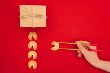 cropped shot of woman taking chinese fortune cookie with chopsticks, Chinese New Year concept