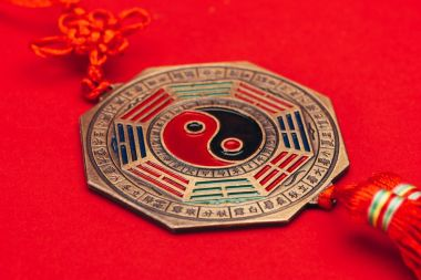 close-up shot of traditional chinese yin and yang talisman on red surface
