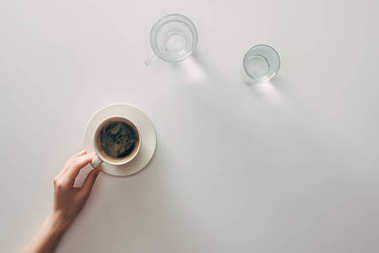 top view of female hand with cup of coffee and glasses with water on grey